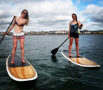 Emma and Hazel stand up paddle boarding in Kilkee Co Clare